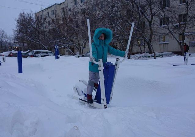 Девочка занимается на уличных тренажерах