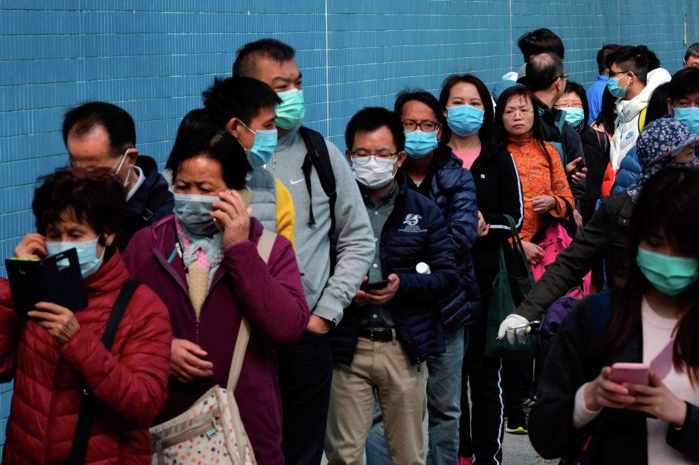 Люди стоят в очереди, чтобы купить маски для лица, чтобы предотвратить вспышку нового коронавируса, в Гонконге, Китай