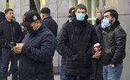 Люди в масках в аэропорту Алматы ожидают прибытия рейса с Хайнаня