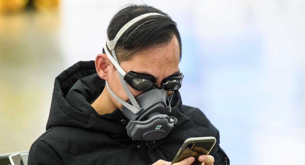 Пассажир поезда в маске на платформе железнодорожного вокзала в Пекина