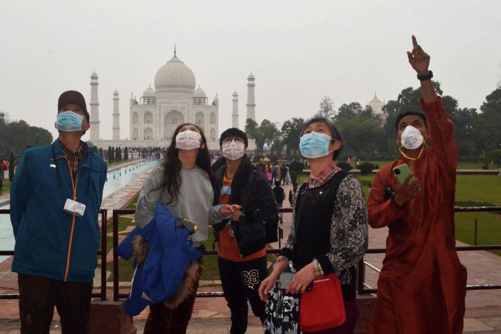 Китайские туристы в защитных масках на экскурсии в Тадж-Махале в Агре, Индия