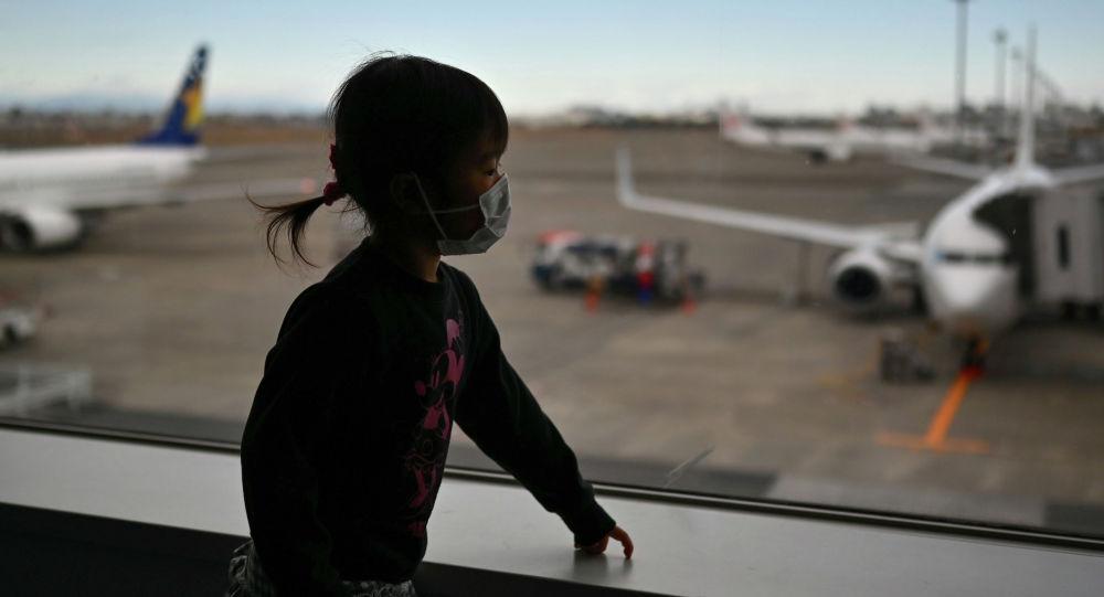 Девочка смотрит из окна аэропорта