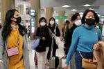 Люди в защитных масках для предотвращения заражения коронавирусом покидают аэропорт