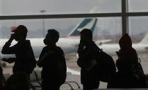 Люди в защитных масках в очереди в аэропорту
