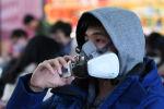 Бейжің вокзалында маска киіп тұрған адам