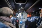 Офицер в защитной одежде инструктирует пассажиров самолета