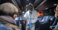 Офицер в защитной одежде инструктирует эвакуированных