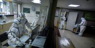 Медицинские работники в защитных костюмах работают в изолированном помещении общественного центра здравоохранения в Ухани