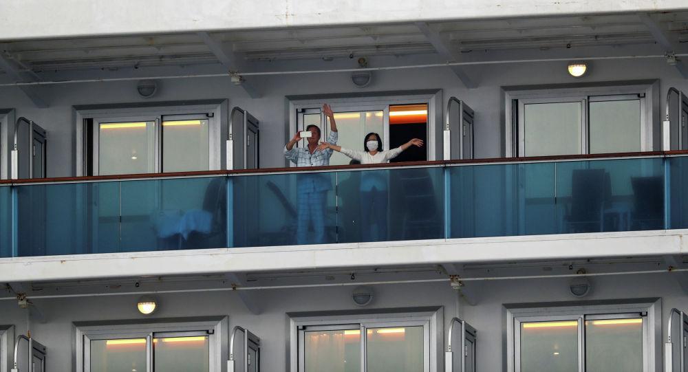 Пассажиры машут с круизного лайнера Diamond Princess в Иокогаме