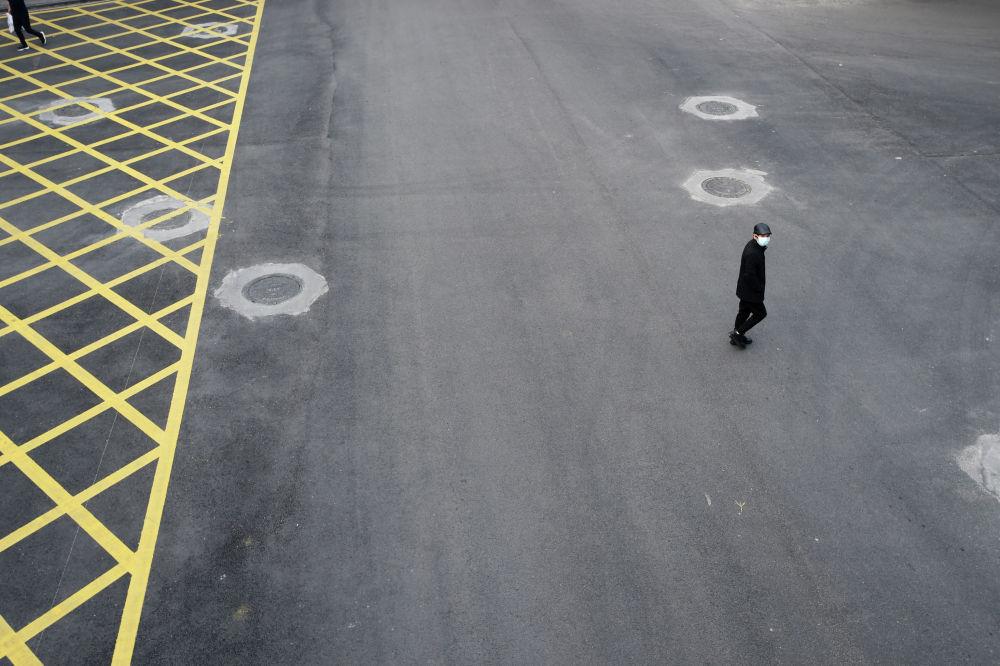 Человек в защитной маске пересекает опустевшую улицу в Ухане