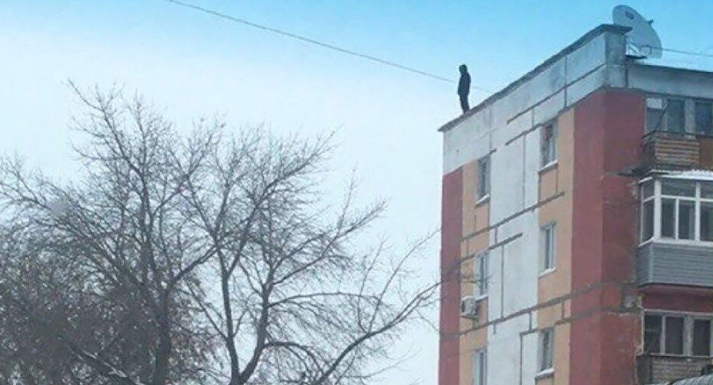 Мужчина на крыше дома в Рудном