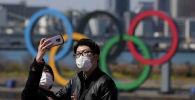 Люди делают селфи под олимпийскими кольцами в Токио, Япония