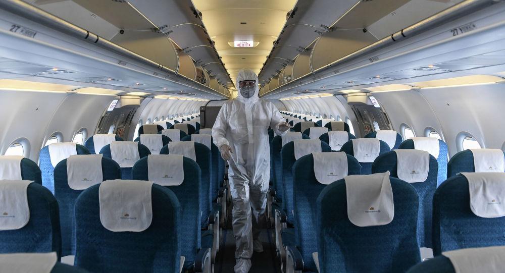Рабочий в защитном костюме дезинфицирует самолет
