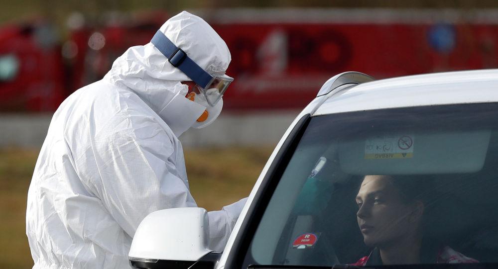 Пассажирам автомобиля измеряют температуру для контроля по коронавирусу