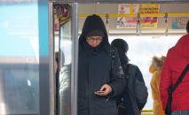 Пассажир автобуса в Нур-Султане со смартфоном в руках