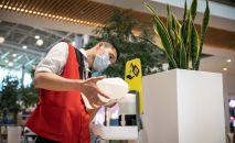 Сотрудник торгового центра наливает антисептик для обработки рук