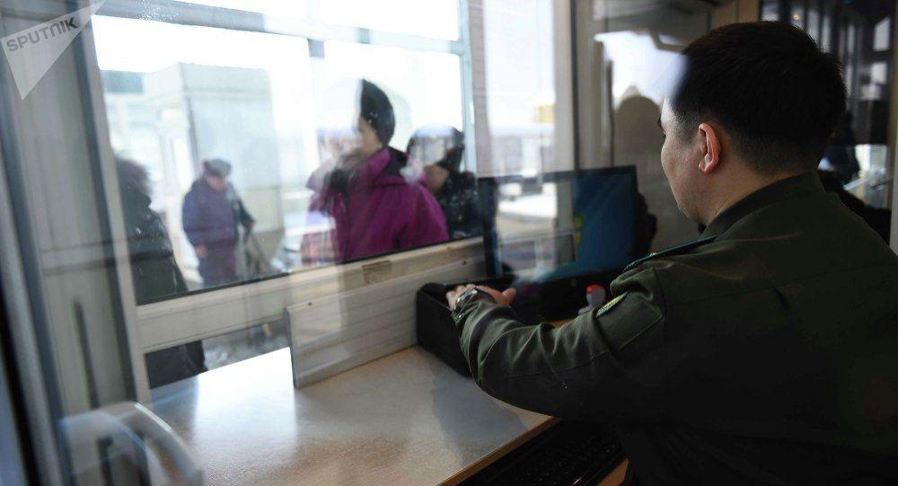Сотрудник КПП кыргызско-казахской границы проверяет документы у граждан, архивное фото