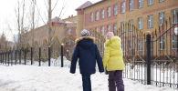 Дети возле здания школы во время каникул