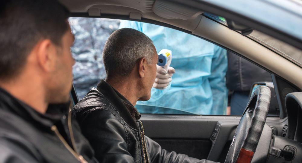Медицинский работник проверяет температуру у водителя на КПП на выезде из города