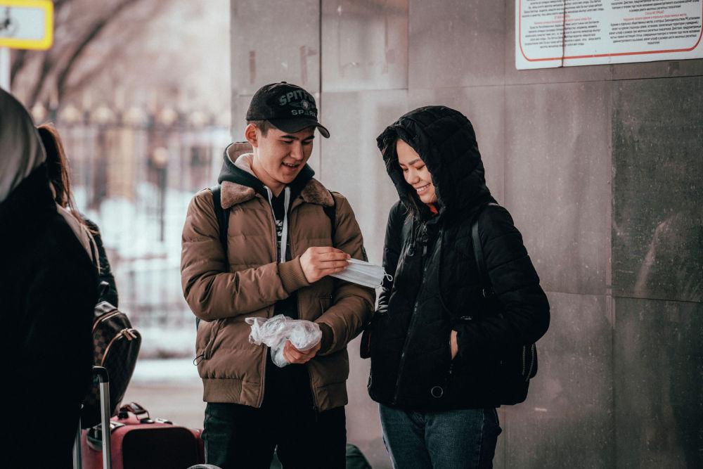 Люди делятся масками у желехнодорожного вокзала Нур-Султана накануне карантина