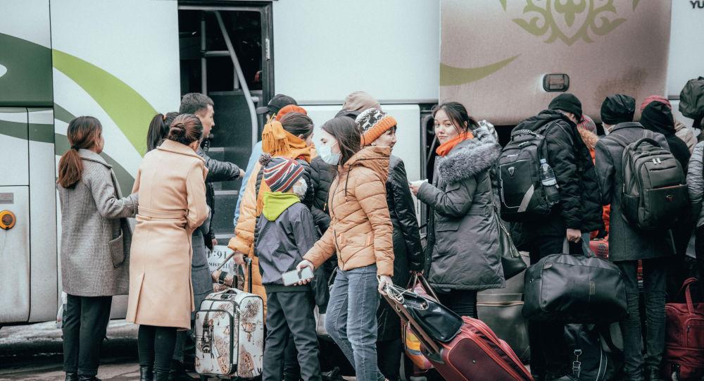 Люди садятся в междугородний автобус накануне каратина в Нур-Султане