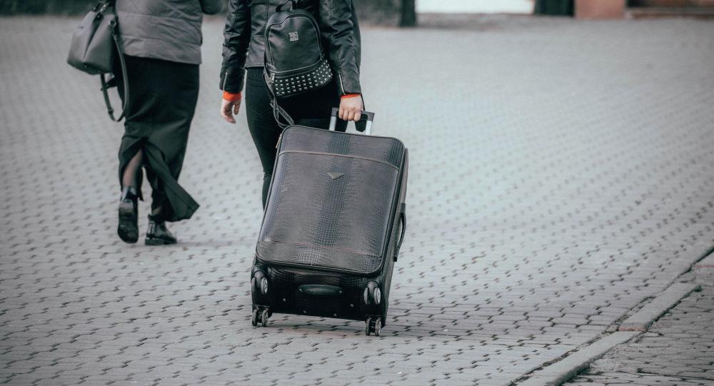 Девушка с чемоданом у вокзала