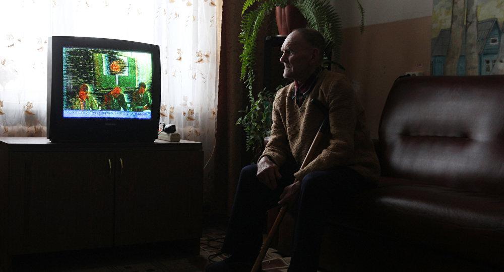 Теледидар көріп отырған ер адам