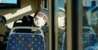 Девушка в маске едет в маршрутном автобусе в Нур-Султана после введения карантина