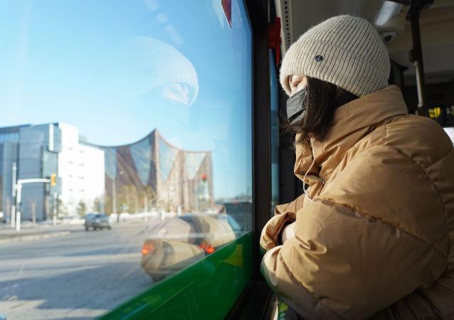 Девушка в маске едет в автобусе в Нур-Султане после введения карантина