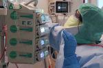 Медицинский работник в защитном костюме проверяет датчики