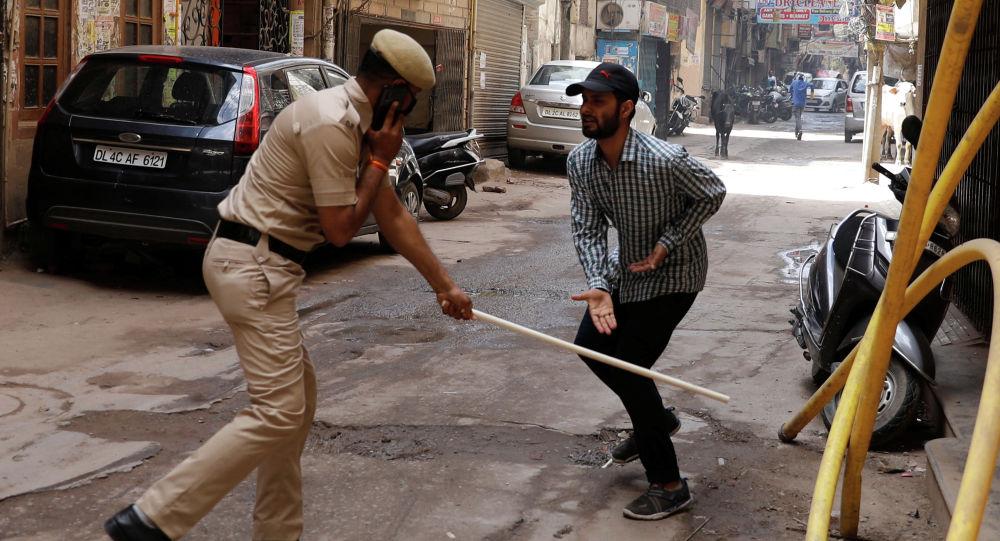 Полицейский бьет палкой прохожего за нарушения карантина в в Нью - Дели, Индия