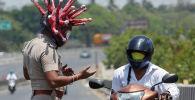 В Индии полицейский в шлеме с изображением коронавируса останавливает водителей и просит сидеть дома