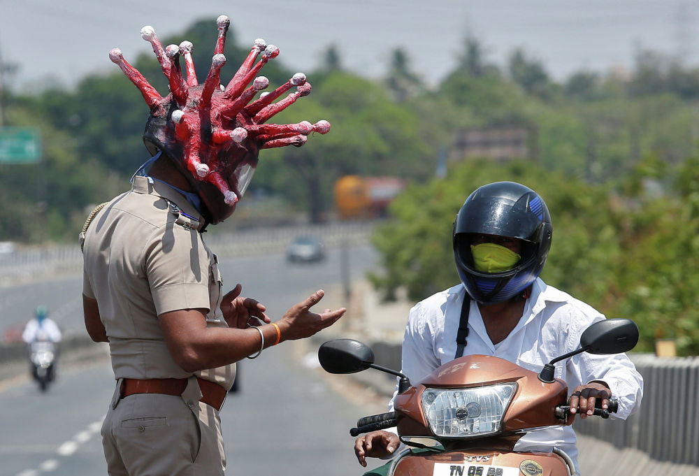 Rajesh Babu, a police officer, wearing a helmet depicting coronavirus, requests a commuter to stay at home during a 21-day nationwide lockdown to limit the spreading of coronavirus disease (COVID-19), in Chennai, India, March 28, 2020. REUTERS/P. Ravikumar