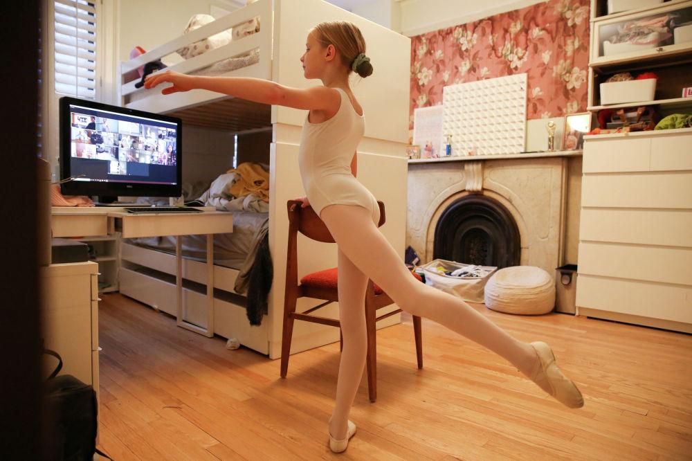 Девочка занимается балетом вместе с подругами в режиме видеоконференции