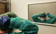 Врач надевает защитный костюм перед зеркалом в больнице с коронавирусом