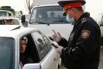 Сотрудник правоохранительных органов в маске беседует с водителем