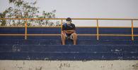 Мужчина в защитной маске на пустом стадионе