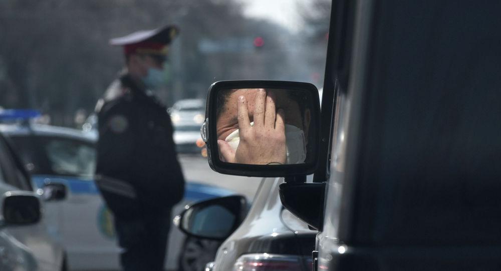 Мужчина в защитной маске отражается в боковом зеркале автомобиля в Алматы