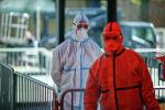 Медики в защитных костюмах готовятся принять пациента с коронавирусом