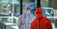 Қорғаныш костюмін киген дәрігерлер пациентті алуға бара жатыр