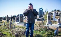 Мужчина молится во время обряда похорон на мусульманском кладбище, архивное фото