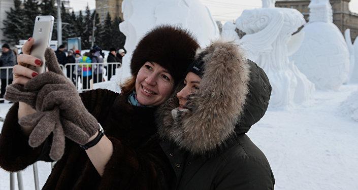 Женщины делают селфи на фоне фигур из снега