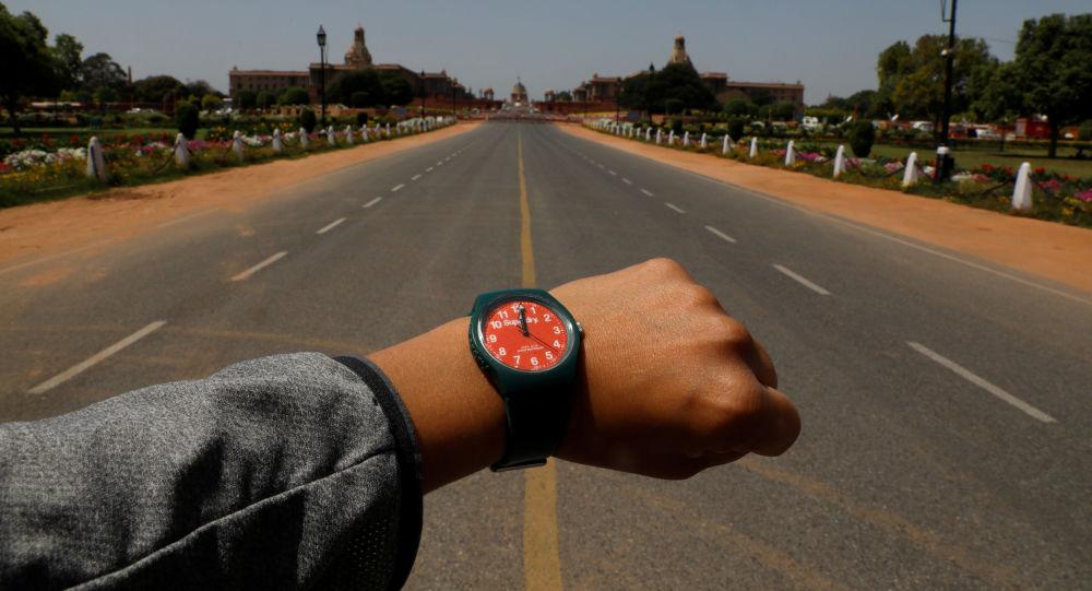 Показывающие полдень наручные часы на фоне пустого проспекта Раджпатх в Нью-Дели в период пандемии коронавируса