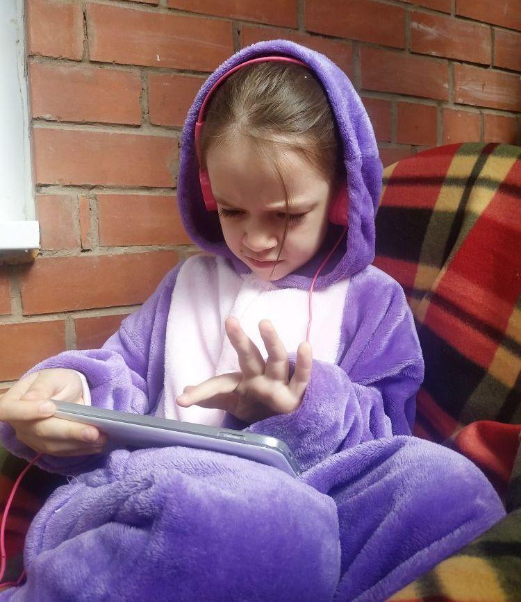 Ребенок выполняет занятия на онлайн-платформе дома на балконе