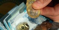 Деньги, тенге монеты в руках