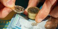 Деньги в руках монеты банкноты тенге