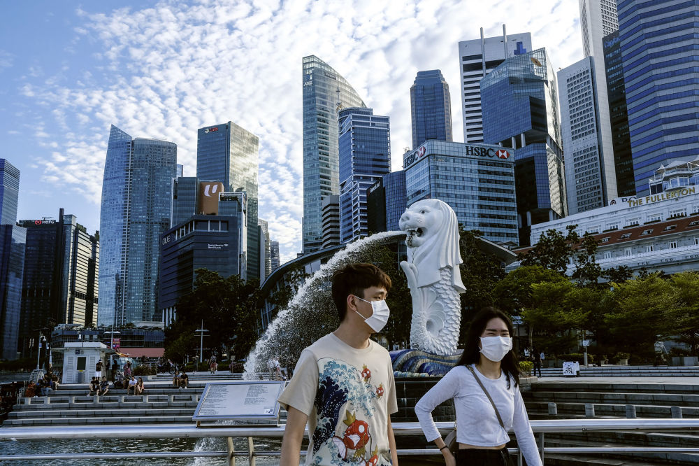 In this March 14, 2020, photo, a couple wearing face masks walk past the Merlion statue in Singapore. As the virus outbreak spreads ever further, it's becoming clear that some strategies are more likely to succeed in containing it: pro-active efforts to track down and isolate cases, access to basic, affordable public health and clear, reassuring messaging from leaders.