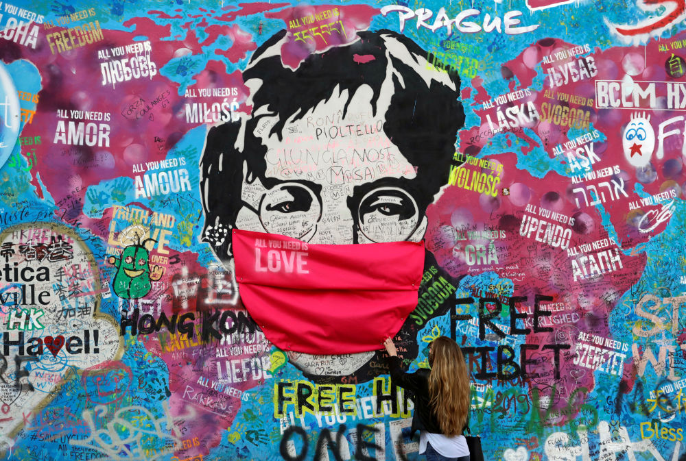A woman wearing a face mask touches the legendary graffiti-covered John Lennon Wall as the spread of the coronavirus disease (COVID-19) continues in Prague, Czech Republic, April 6, 2020.