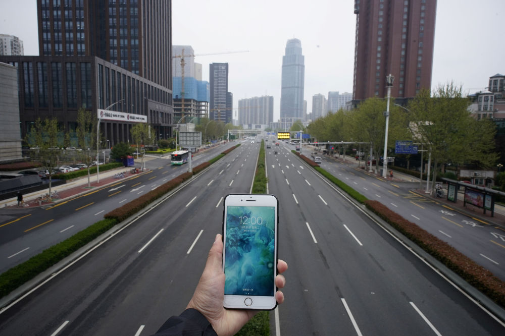 A mobile phone showing the time at noon, is displayed for a photo in front of an almost empty road with low traffic, during the coronavirus disease (COVID-19) outbreak, in Wuhan, Hubei province, China, March 31, 2020.