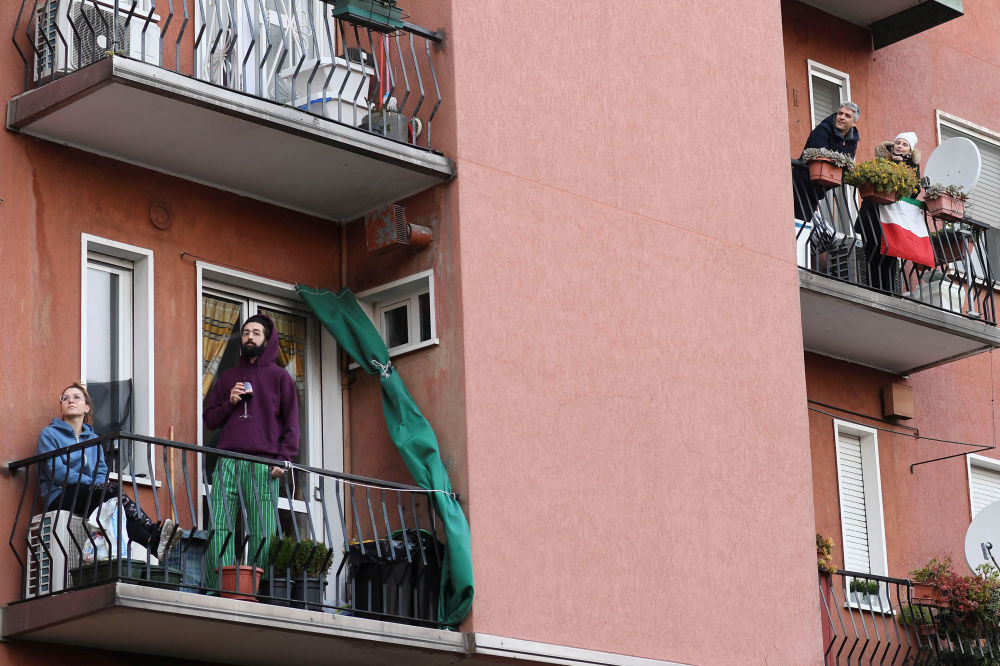 People listen to music as a neighbor plays the guitar and sings from a balcony to raise morale on the sixth day of an unprecedented lockdown across of all Italy imposed to slow the outbreak of coronavirus in Milan, Italy March 15, 2020.